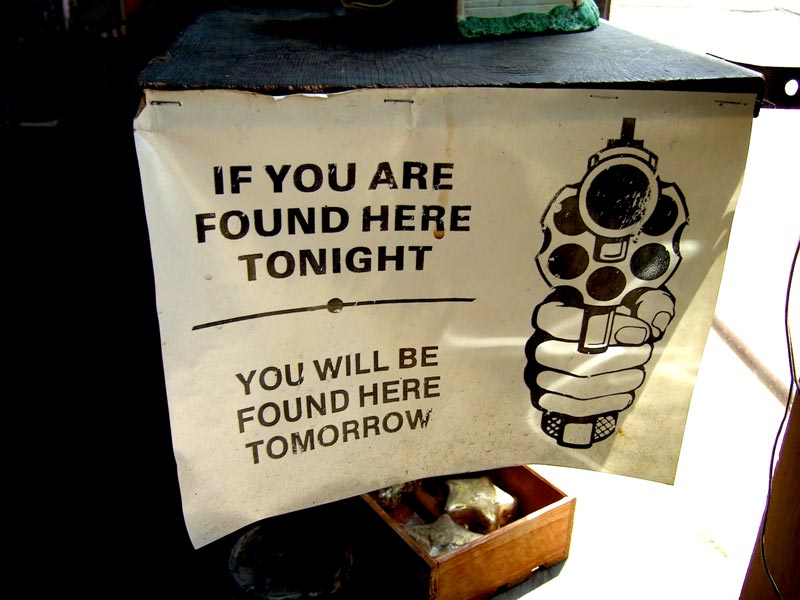 "Greewood Store Sign says ""If youare Found Here Tonight, You will be Found Here Tomorrow"" with a gun pointed at the reader."