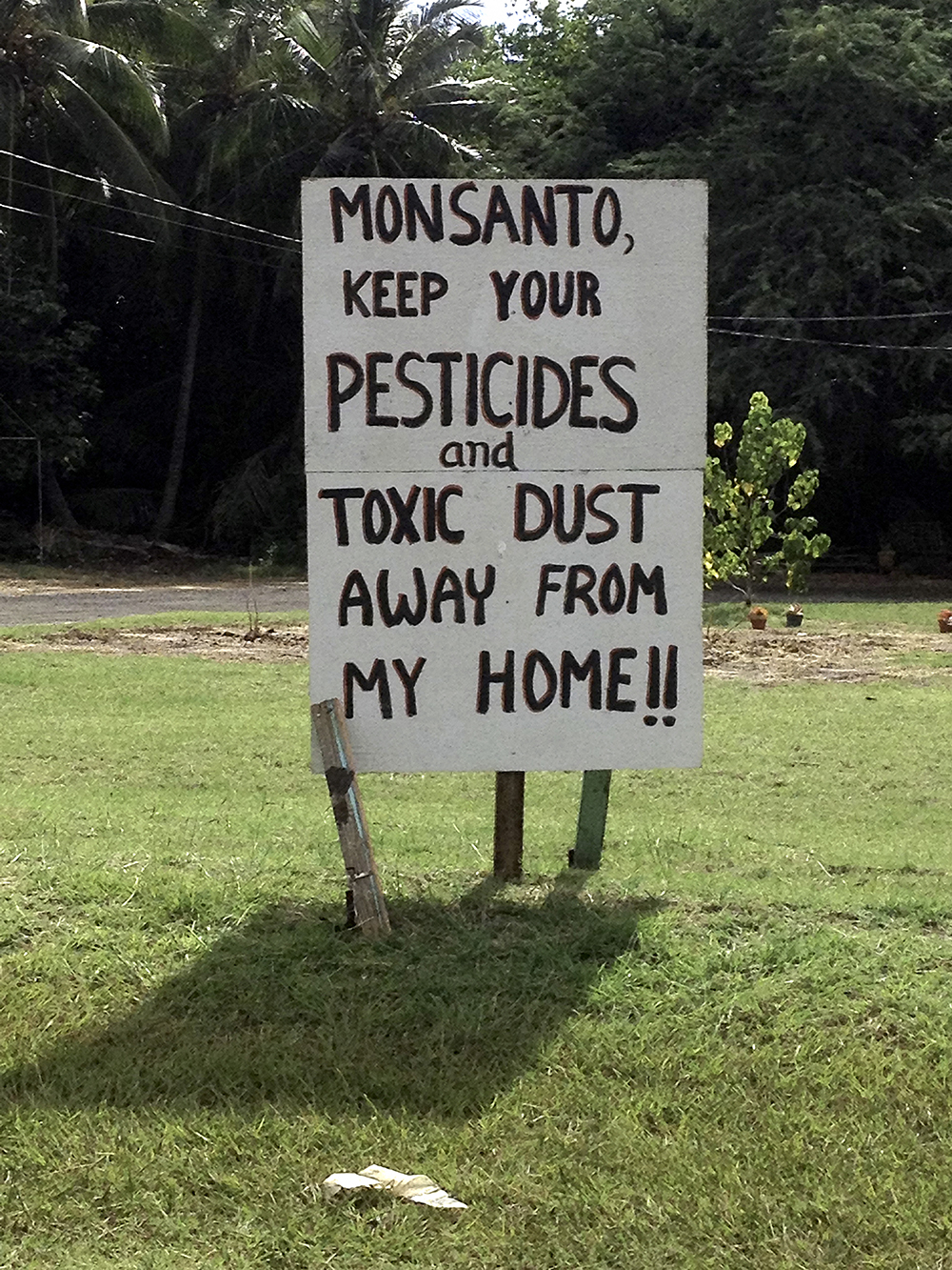 Hand-lettered sign reads: Monsanto, keep your pesticides and toxic dust away from my home!!
