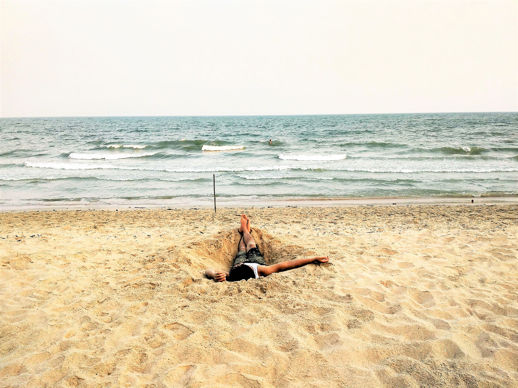 person laying in sand on beach