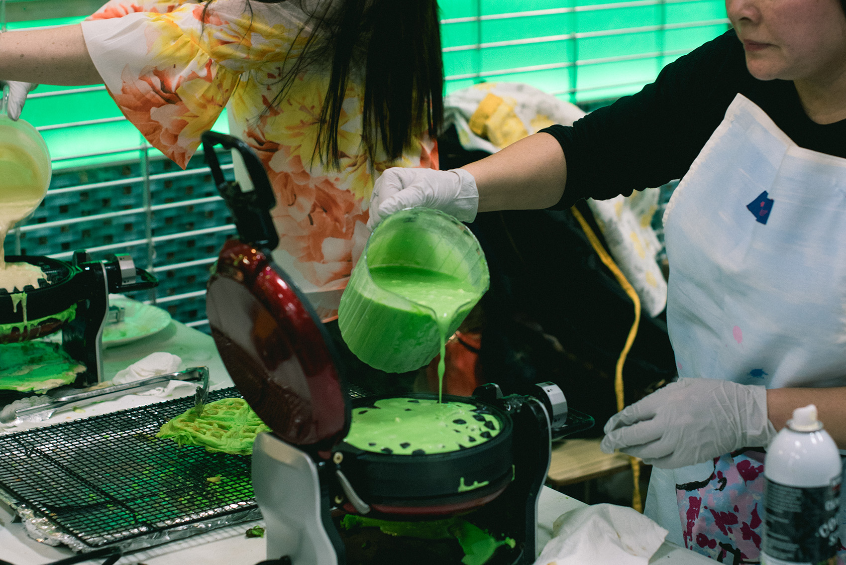 Photo of pandan waffles being cooked on waffle irons