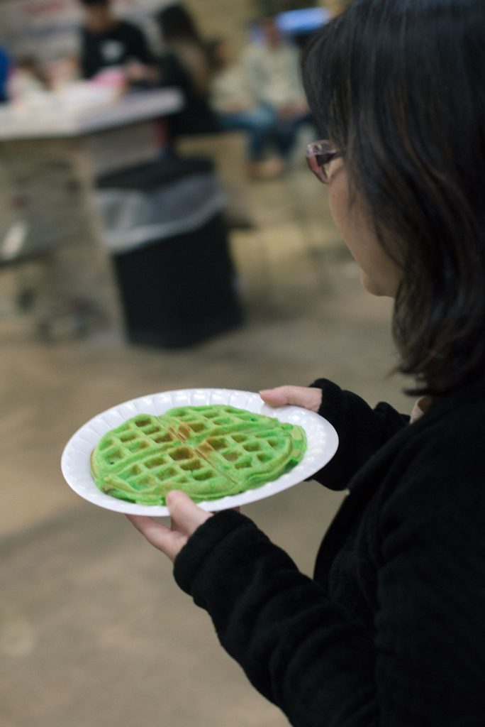 Photo of a woman holding a plate with a pandan waffle