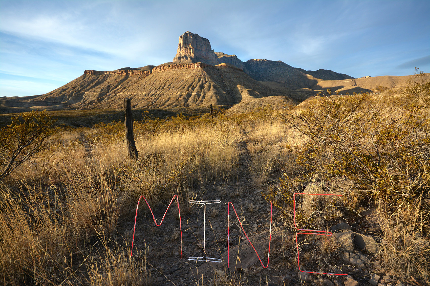 Texas landscape with text sculpture 'MINE'