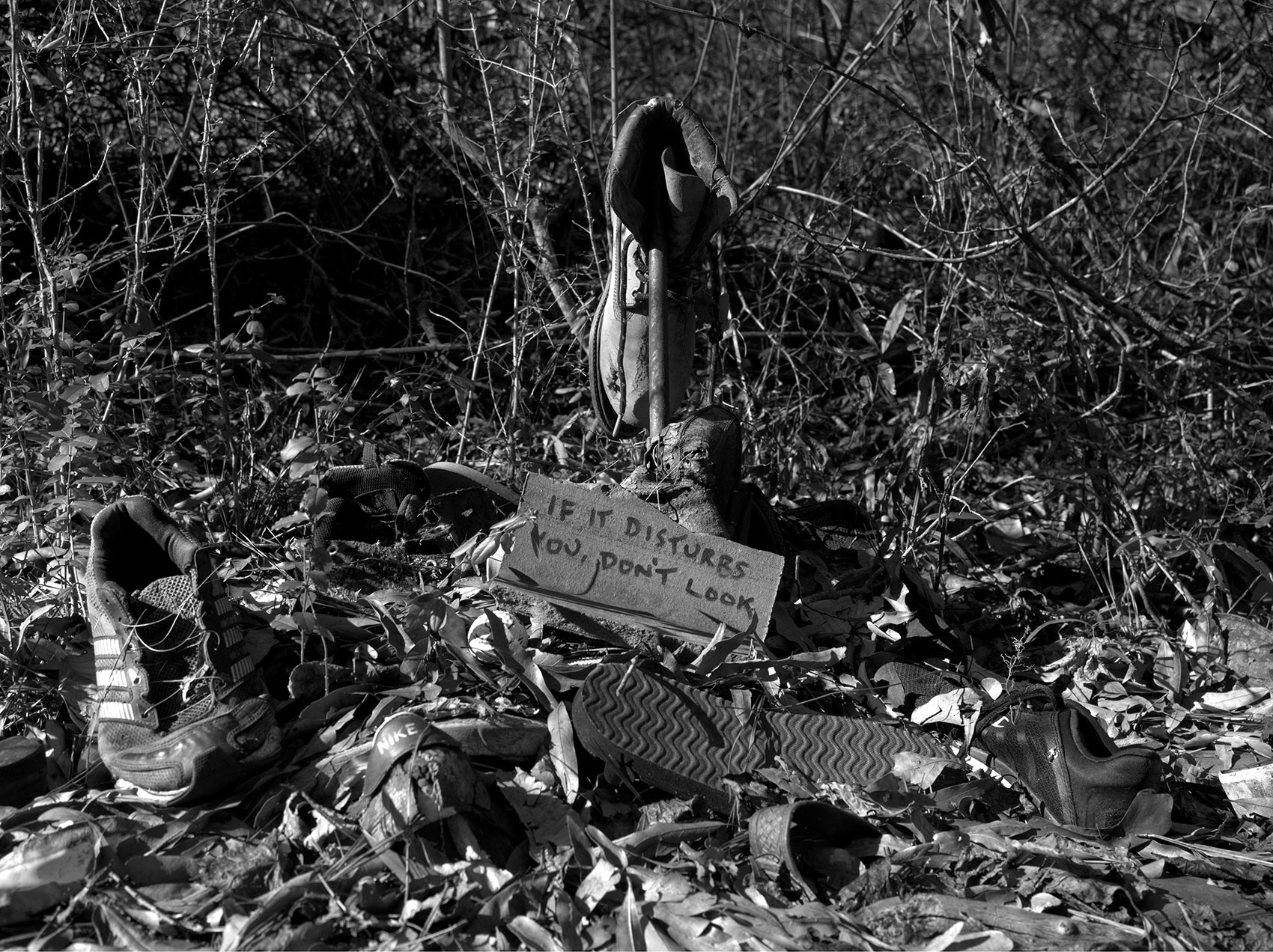 "black-and-white photo of discarded shoes with a sign that reads ""If it disturbs you, don't look"""