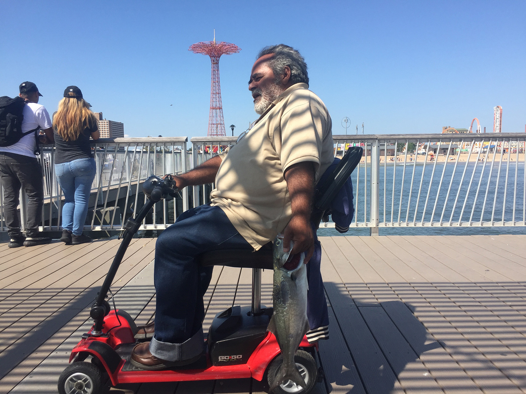 man in electric scooter chair carries a fish by its gills