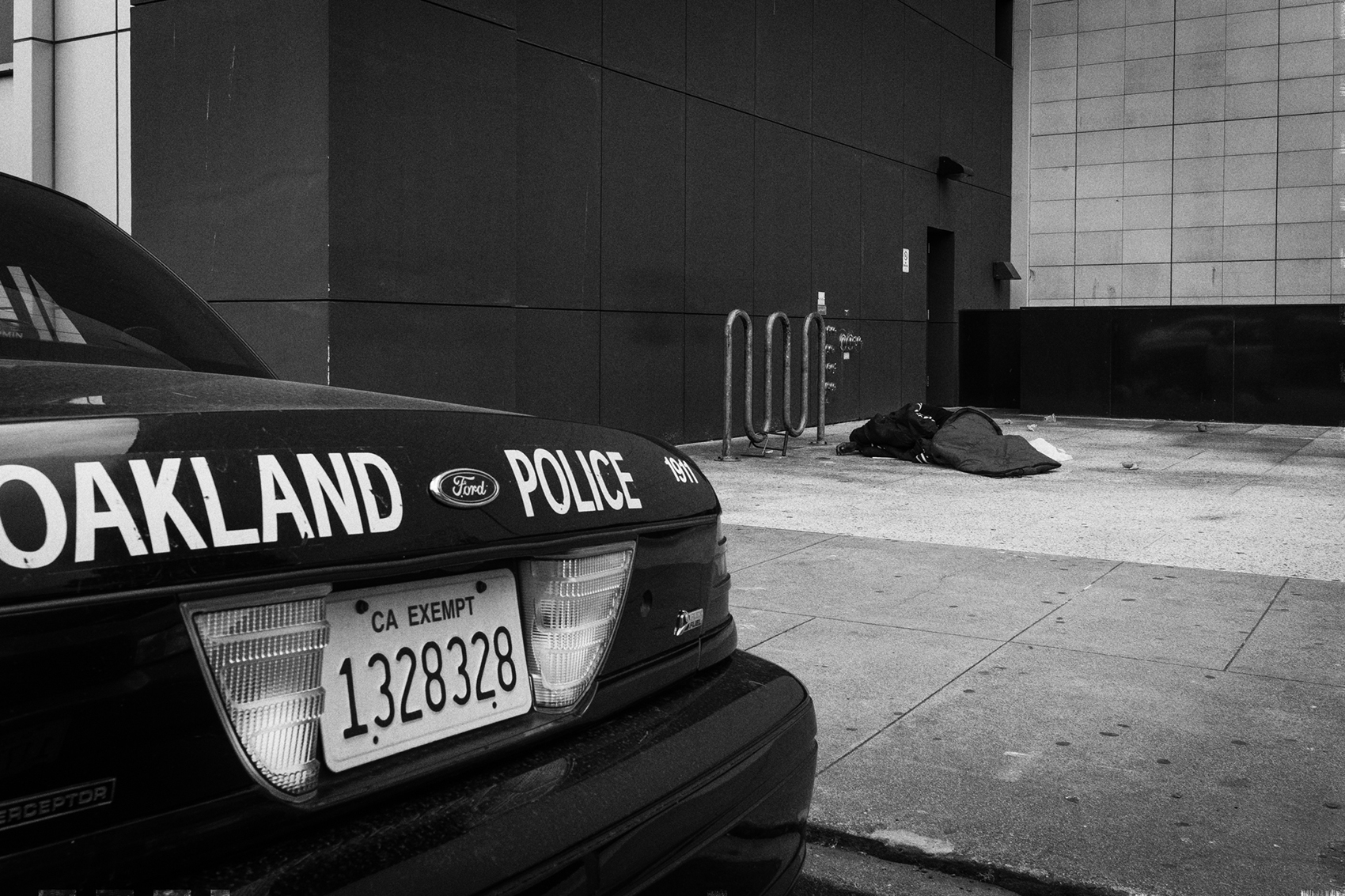 black and white photo of police car in foreground with homeless person sleeping on concrete in background