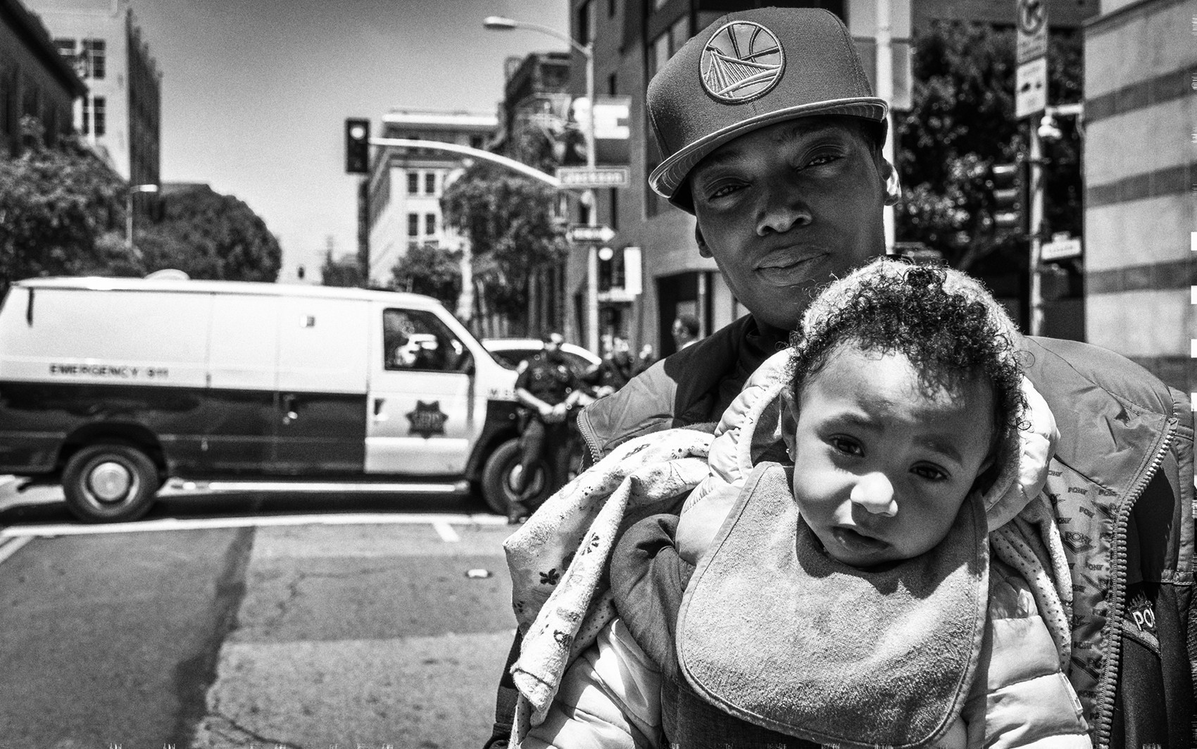 black and white street scene photo featuring parent of color carrying a child