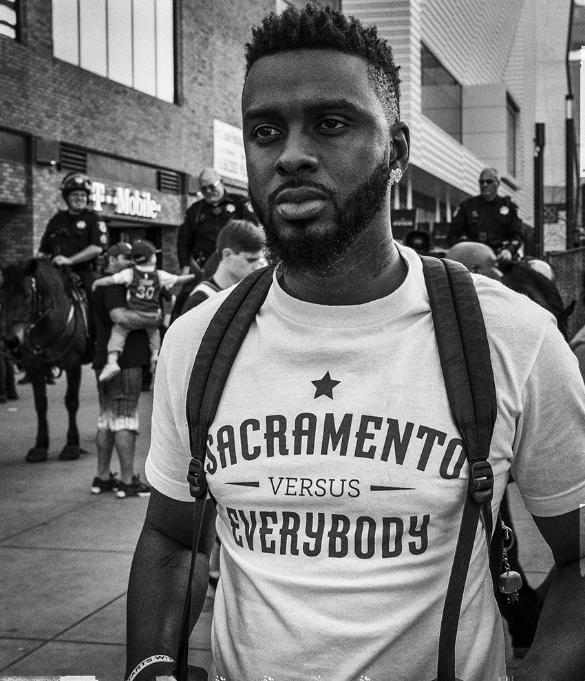 "black and white photo of a man of color wearing a shirt that says ""Sacramento versus Everybody"""