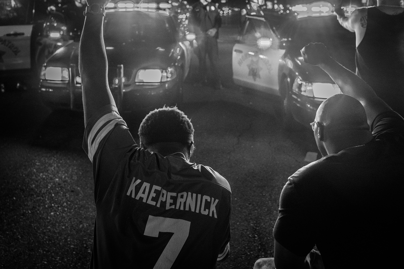 two men, one with a Kaepernick jersey, kneel in front of police cars