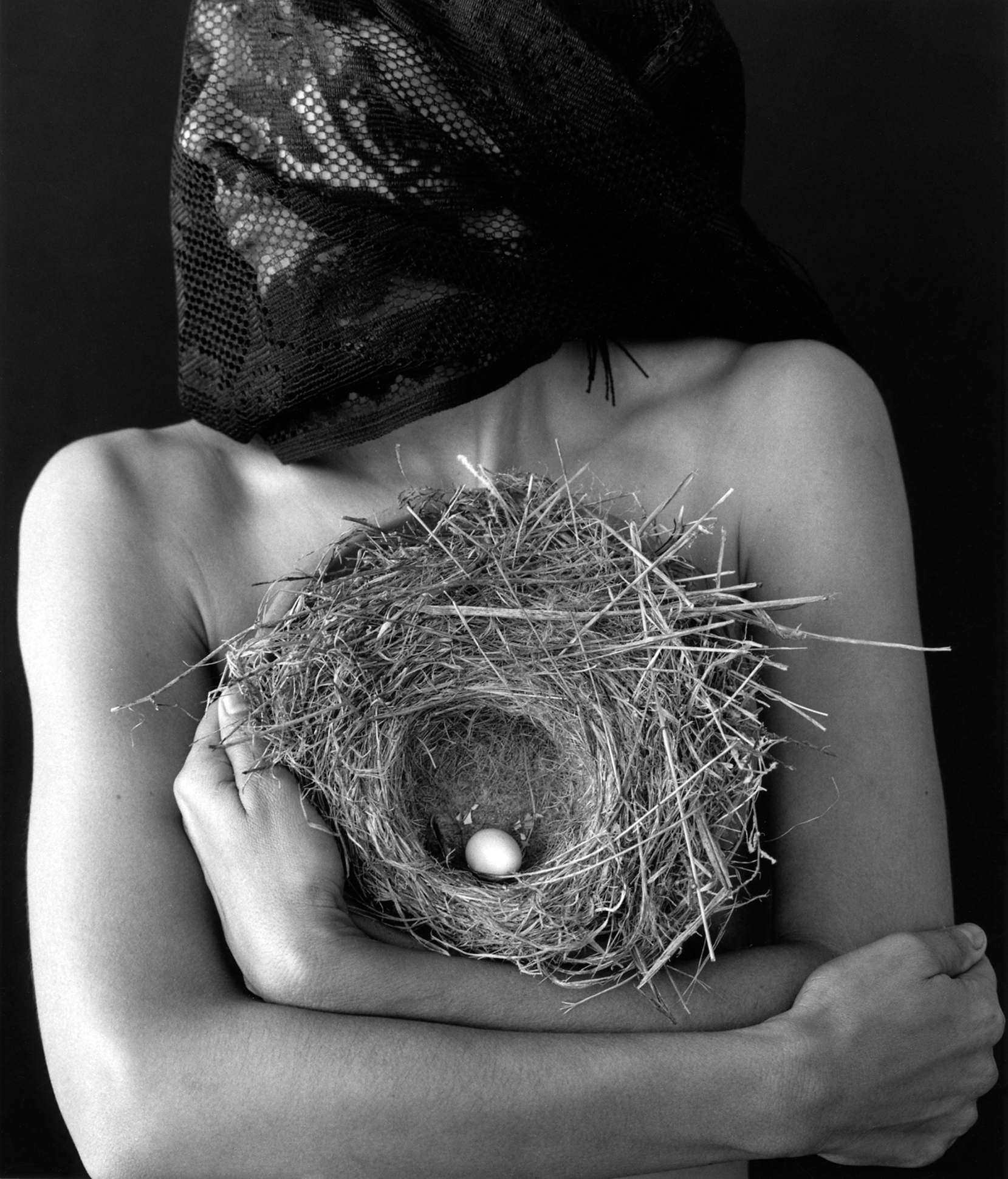 Black and white portrait of a nude woman covered by a nest with an egg, her face partially obscured by a lace veil