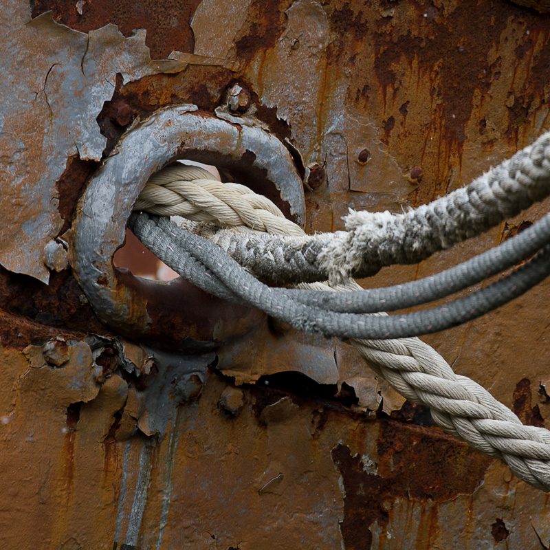 photo of rope and cables in a rusty ship wall