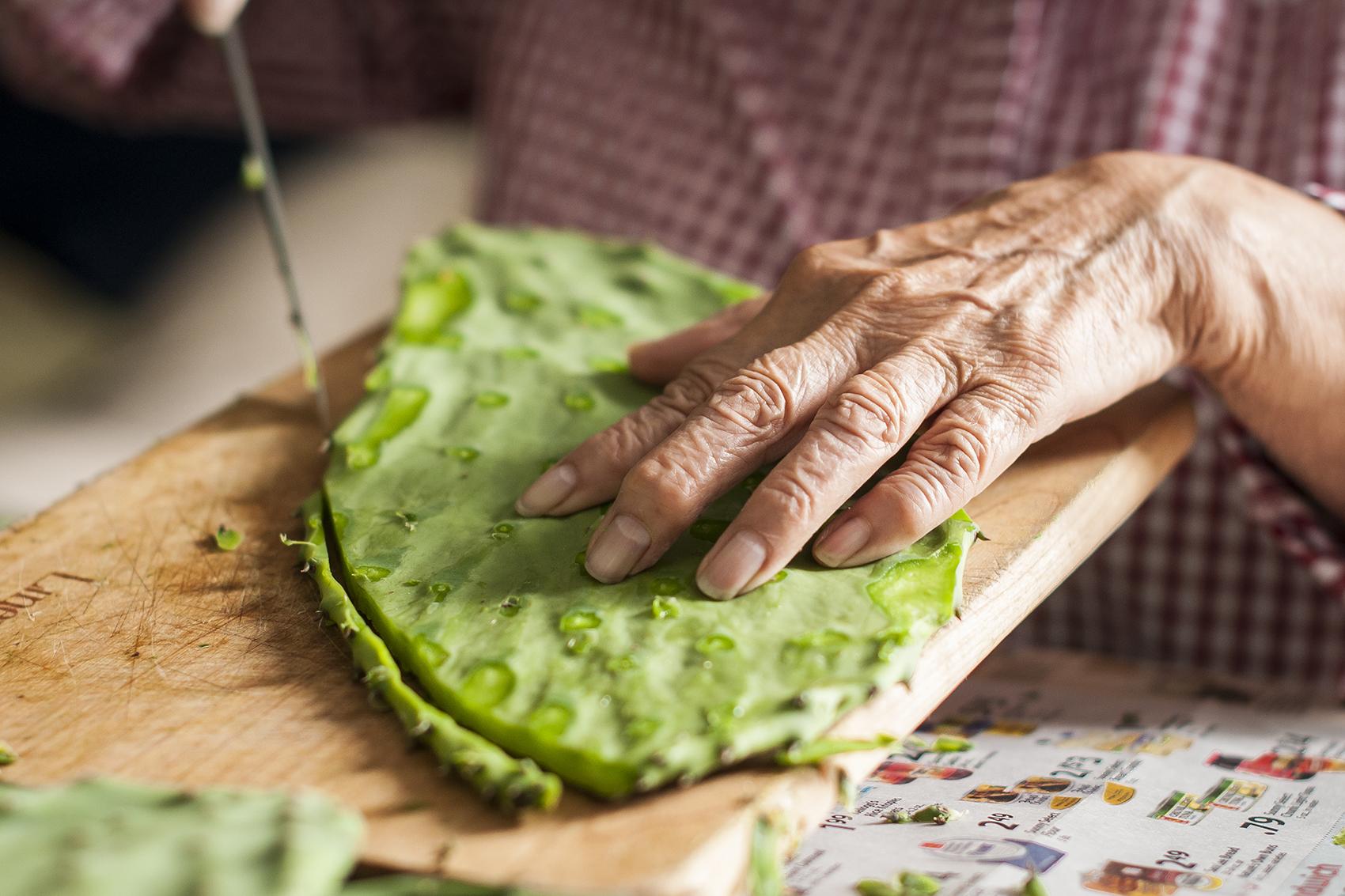 close up photo of a elderly woman's hands preparing nopales