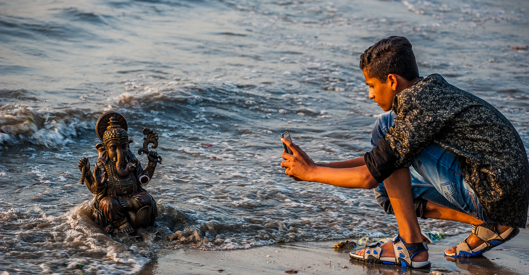 photo of a boy squatting on the shore taking a photo of a sea deity