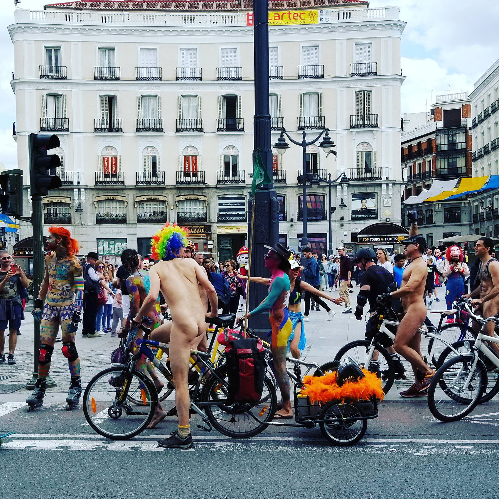 photo of protest on the streets of Madrid featuring colorful outfits, nudity, bicycles