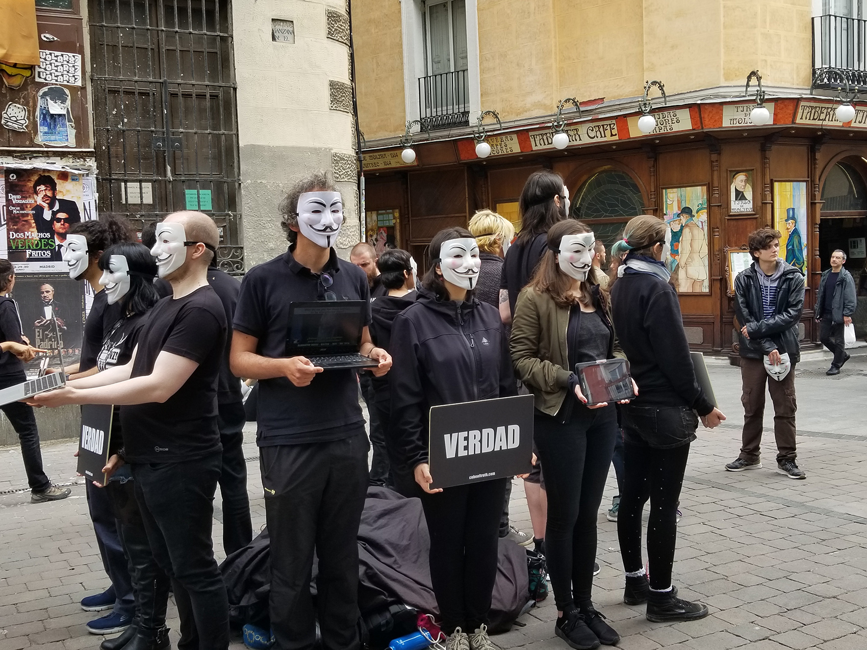 """photo of people on street in Madrid wearing anonymous masks, holding electronic devices and a sign """"Verdad"""" (Truth)"""