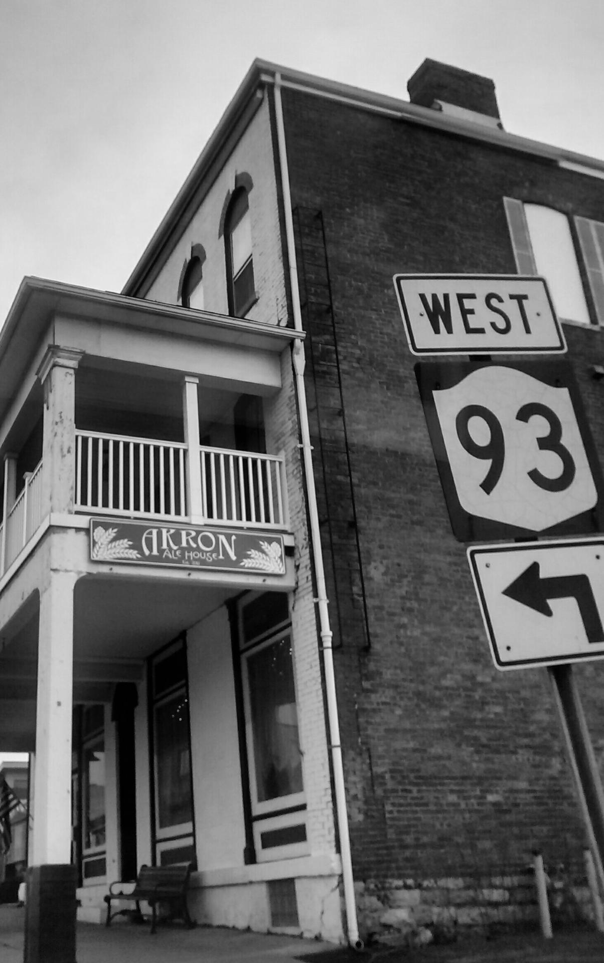 black and white photo of a brick building with AKRON sign and road sign for Hwy 93 West with a left arrow