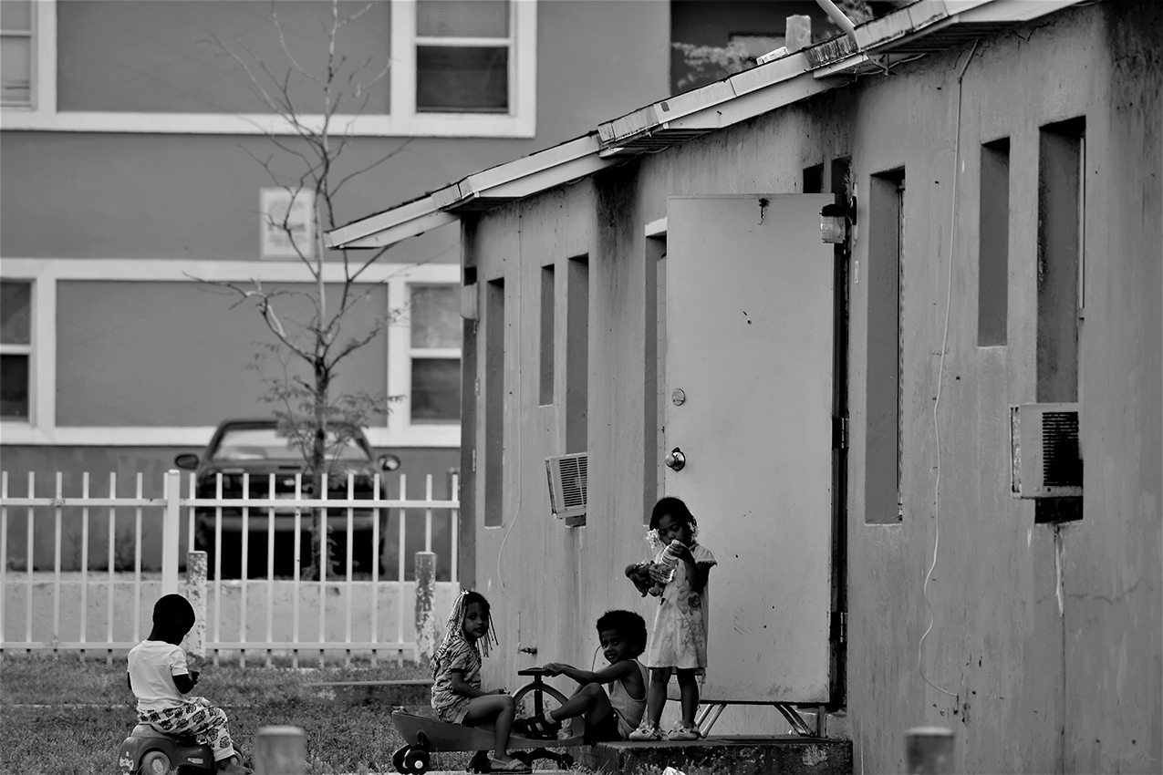 black and white photo of Haitian children playing in the front yard of their house