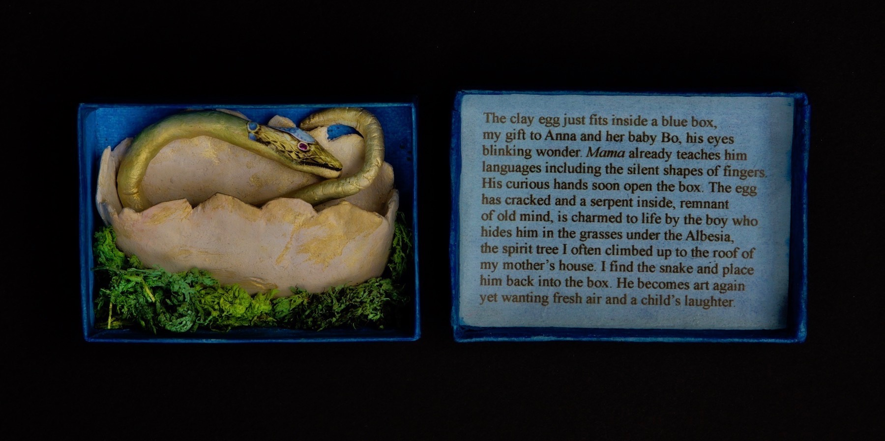 Blue Box by Carrie Albert: photo of a small opened box with a snake sculpture in the left (bottom) half and text in the right (top) half
