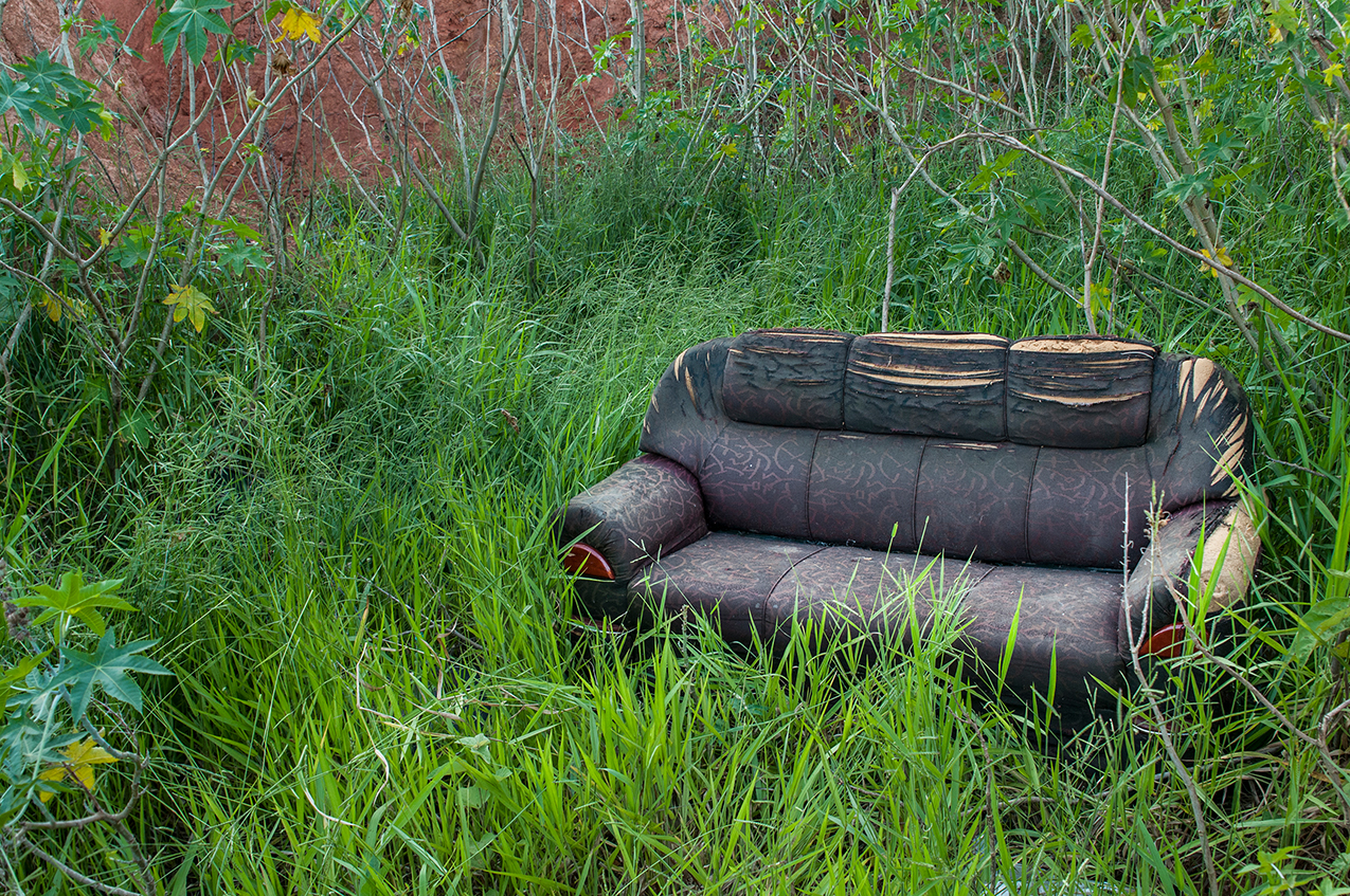 Couch by Guilherme Bergamini: photo of a delapidated couch surrounded by wild grass