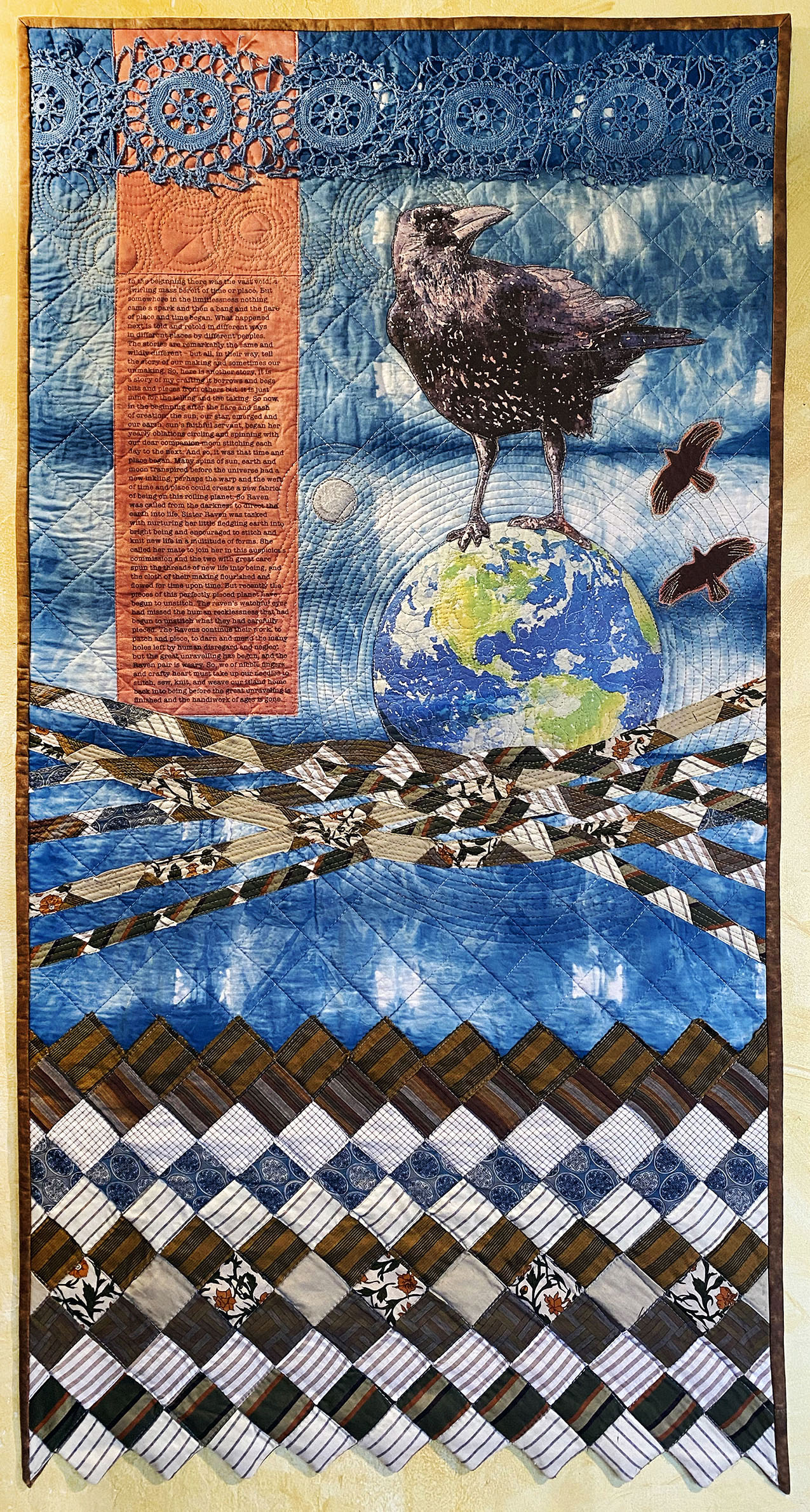 art quilt featuring a raven atop the Earth