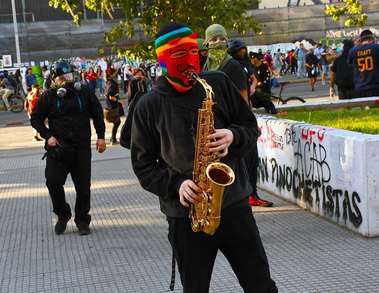 Protester wearing a rainbox mask plays the saxophone in the streets of Santiago