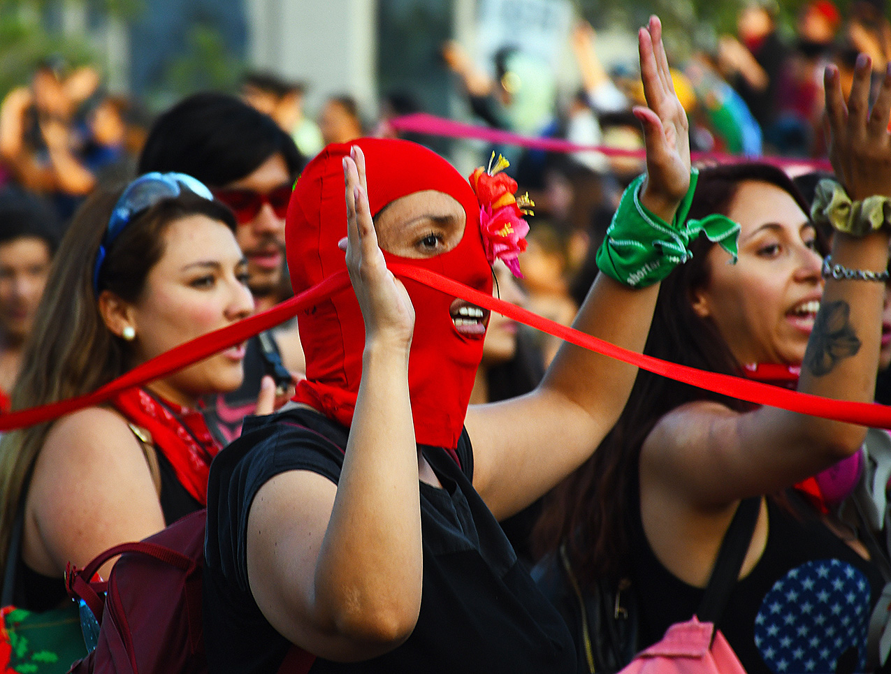Female protesters, including one wearing a red mask, hold their hands in the air