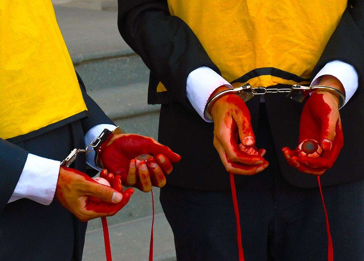 Two sets of hands in handcuffs holding bloody eyeballs during uprising