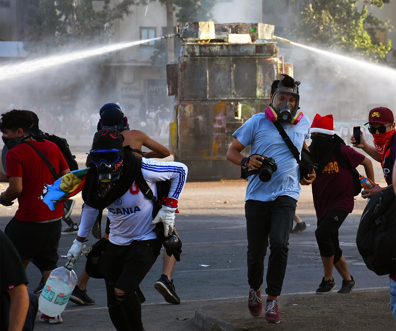 Young people wearing gas masks run away from water cannons in the street during protests