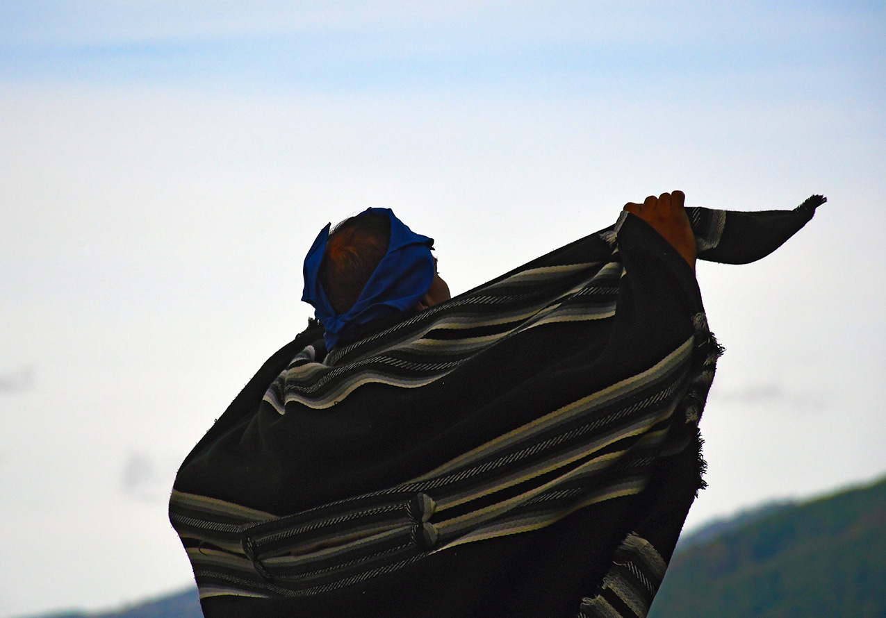 A Chilean and poncho silhouetted against the blue sky