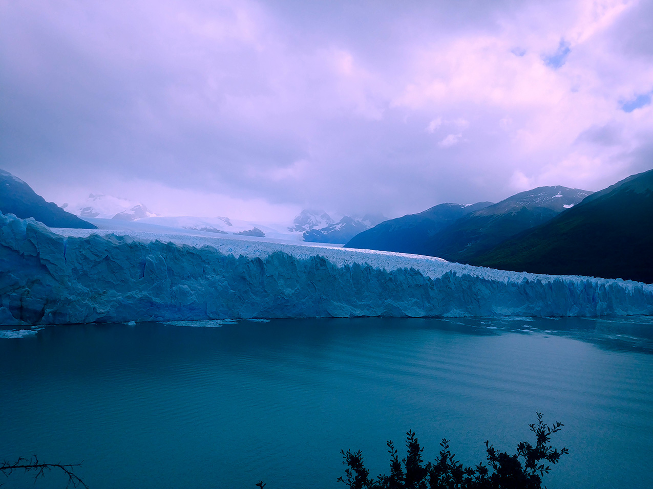 photo of Blue Glacier behind a lake, under a purple cloudy sky
