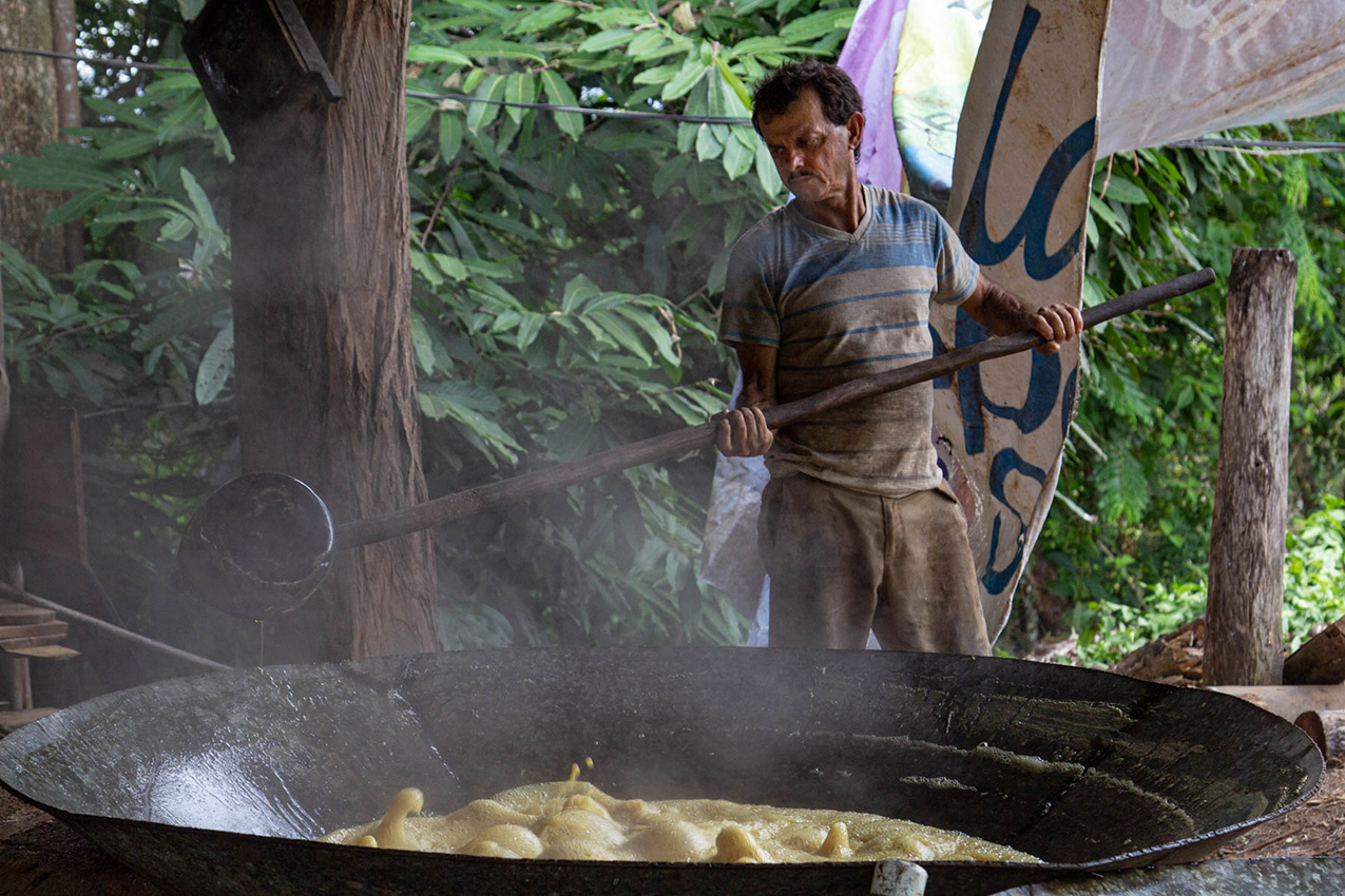 A Costa Rican man holding a large paddle stands next to a huge pan of steaming sugarcane