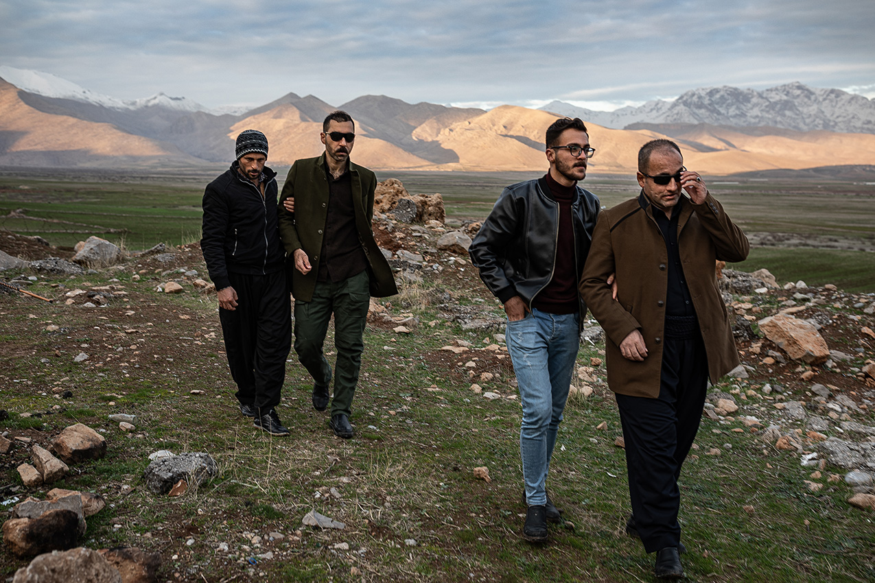 Two blind men wearing sunglasses are each accompanied by another man through a rocky landscape in Iraqi Kurdistan