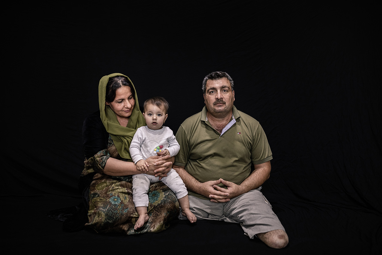 Portrait of a Kurdish family (man, woman and baby) on a black background. The man has both legs amputated.