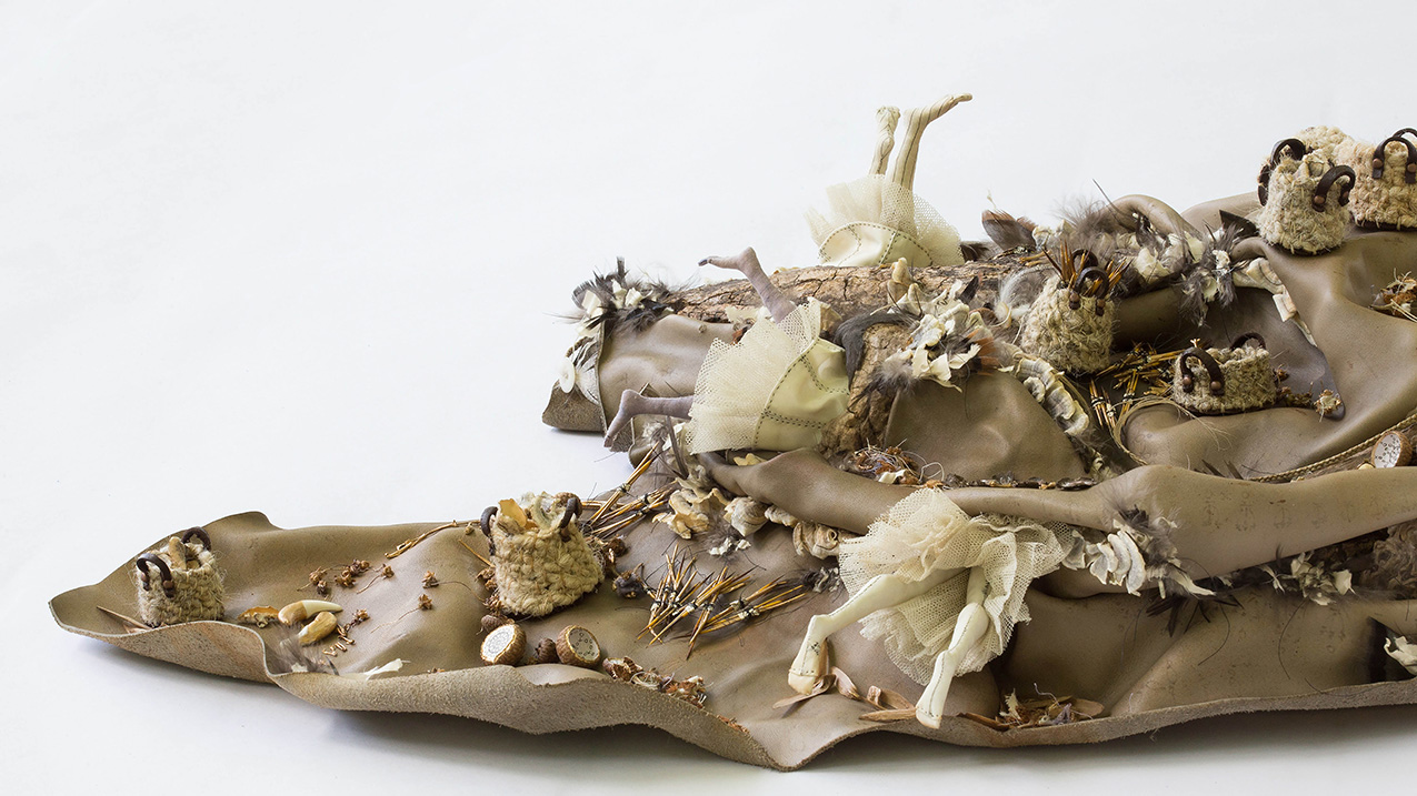 closeup of cloth sculpture adorned with miniature skirted dolls, animal bones, seeds, miniature woven baskets and wood