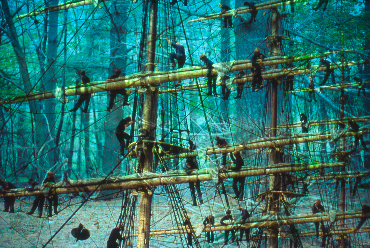 double-exposure photo featuring a forest and men building ship masts