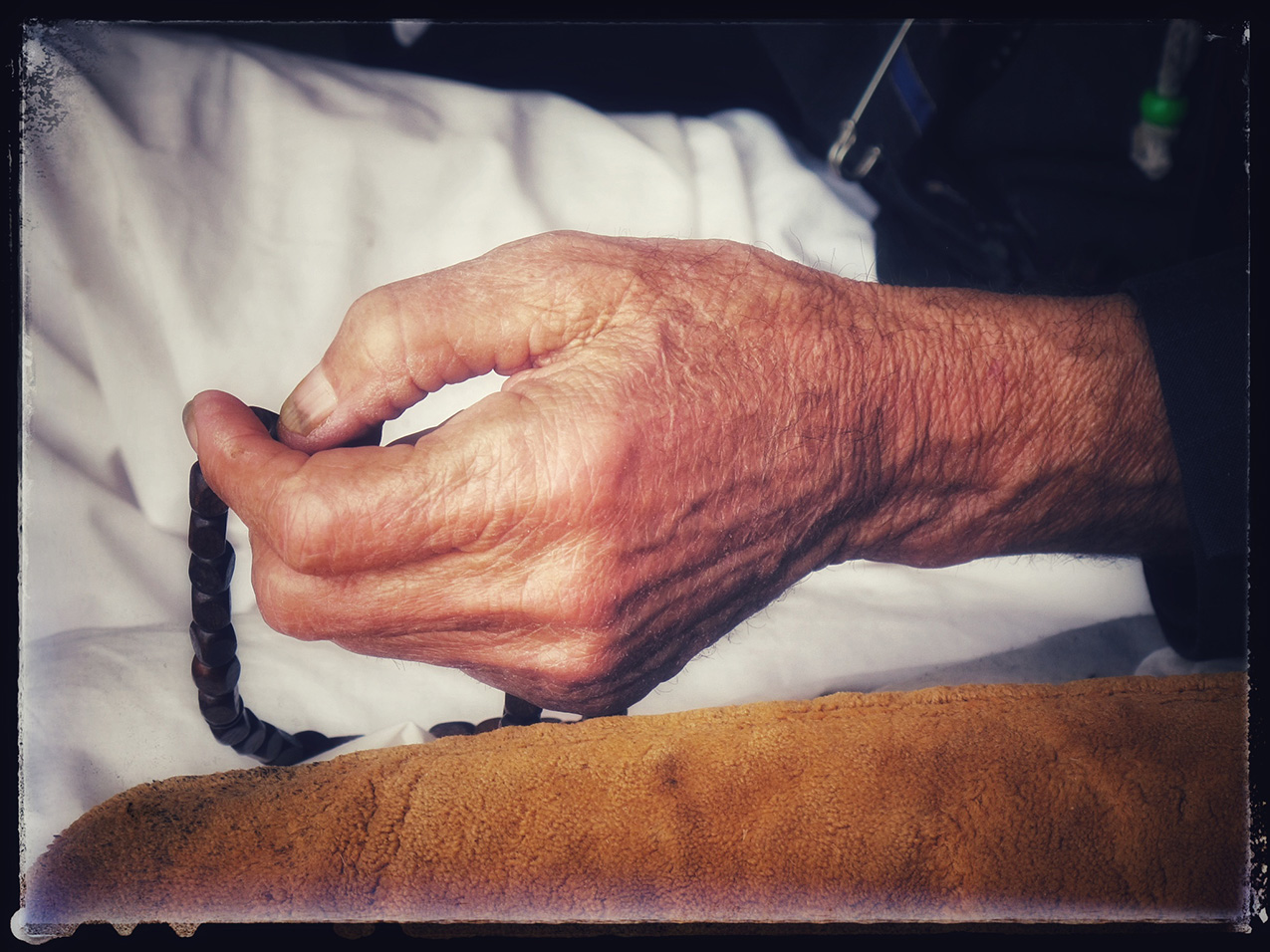 an elderly hand holding rosary beads