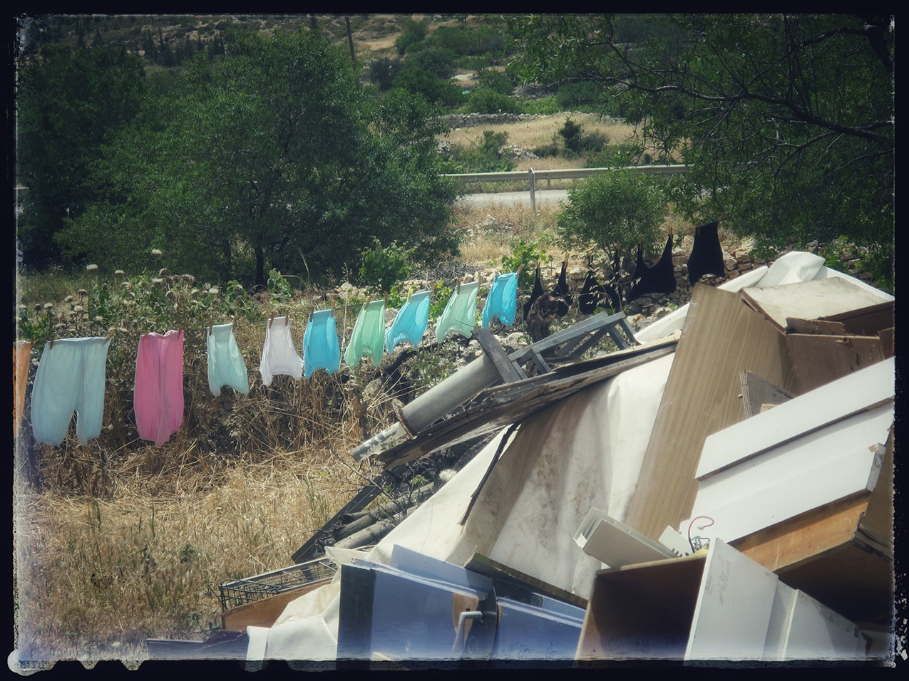 clothes hanging on a clothesline with a large pile of discarded furniture in the foreground