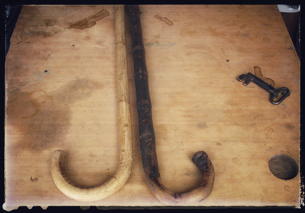 two heavily-used canes and an antique key rest on a worn table