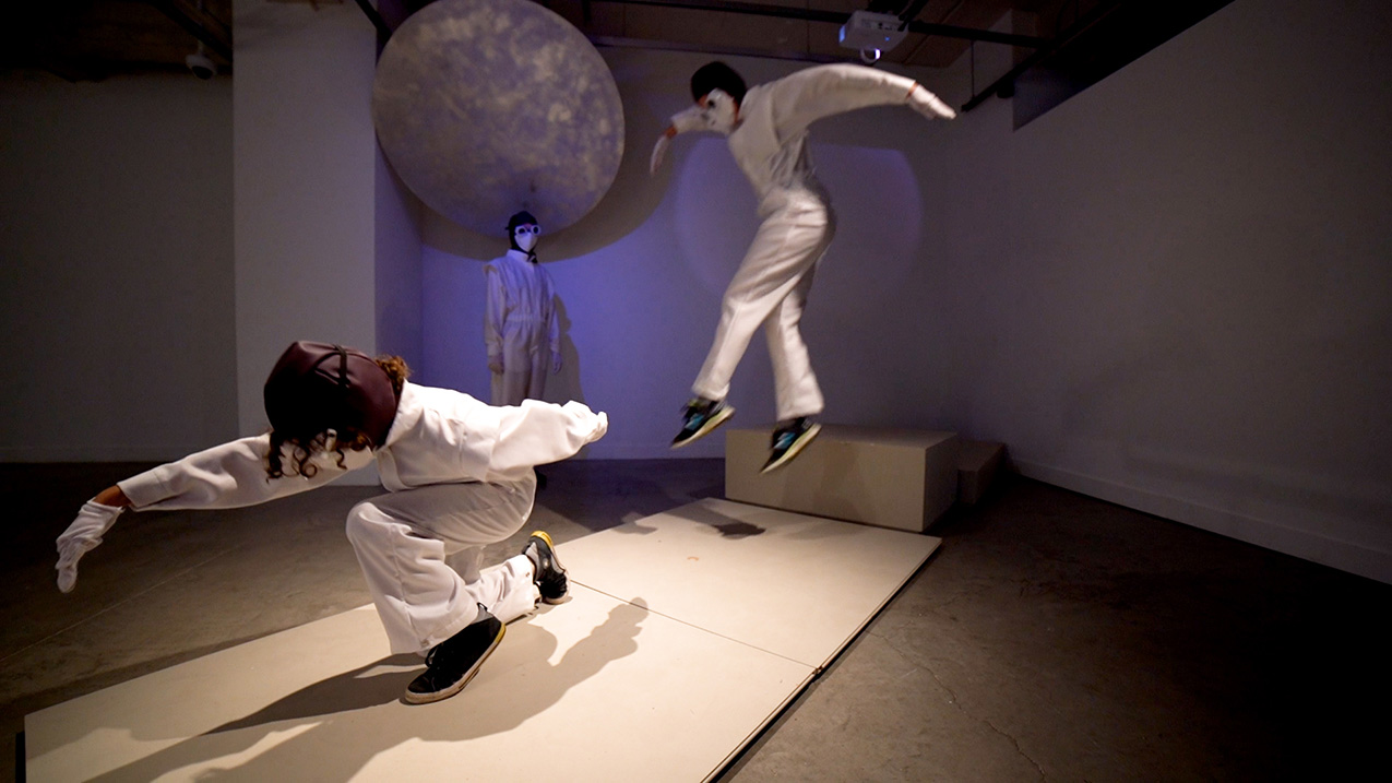 performance artists in white suits, masks and goggles leap in a performance space