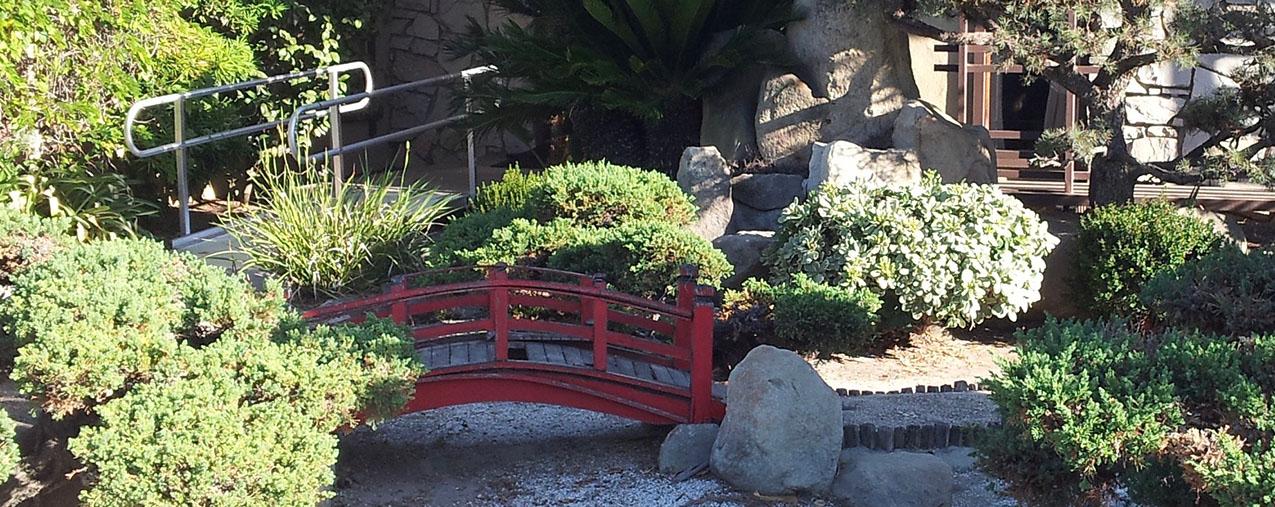 a karesansui niwa (dry garden) featuring a small red moon bridge over a gravel stream