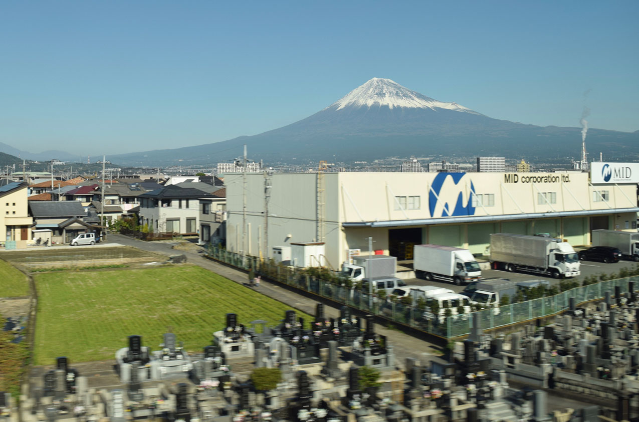Mount Fuji in the distance with a cemetary in the foreground and industrial and residential buildings in the midground