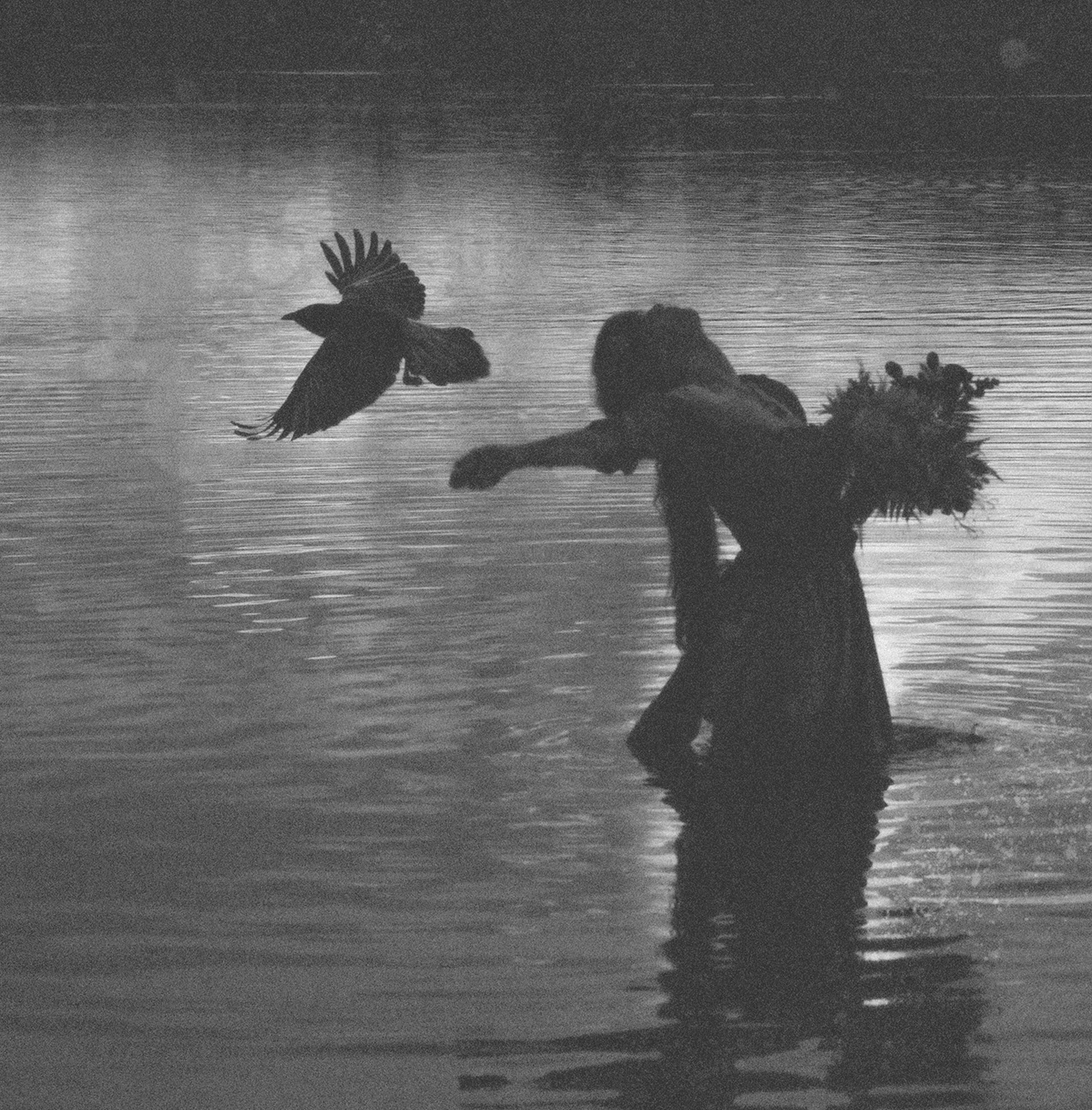 grainy, low-contrast photo of a woman wearing a dress and holding a bouquet standing in a lake; a large bird flies very close by